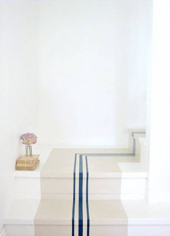 Snug Rug Not all stair runners have to be fabric or carpet. This sweet painted runner brings nautical flair to a white landing. It's a DIY weekend project in the making.