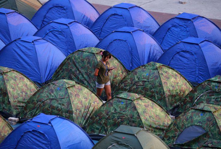 Seorang demonstran anti-pemerintah memeriksa SMS dari HPnya di di antara tenda-tenda di tempat protes di Bangkok, Thailand. (6 Februari 2014)