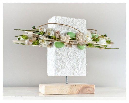 Ciekawa, nowoczesna kompozycja do postawienia. Biała baza została udekorowana kremowymi kwiatkami sola, białymi kwiatkami, muszlami , szklanymi kamykami w kolorze pistacjowym , zielonymi kulkami, suszem i kryształkami. Wysokość kompozycji to ok. 32 cm Szerokość kompozycji 46 cm Kompoz...