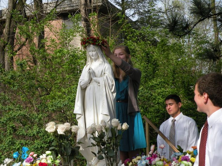 Molly Blasen, an 8th grader, places a crown of fresh-cut red roses on the statue of Mary in the Mary Garden of St. Monica Catholic School, while 8th grader Koty Meadmore looks on. (Photos courtesy of St. Monica Catholic School)