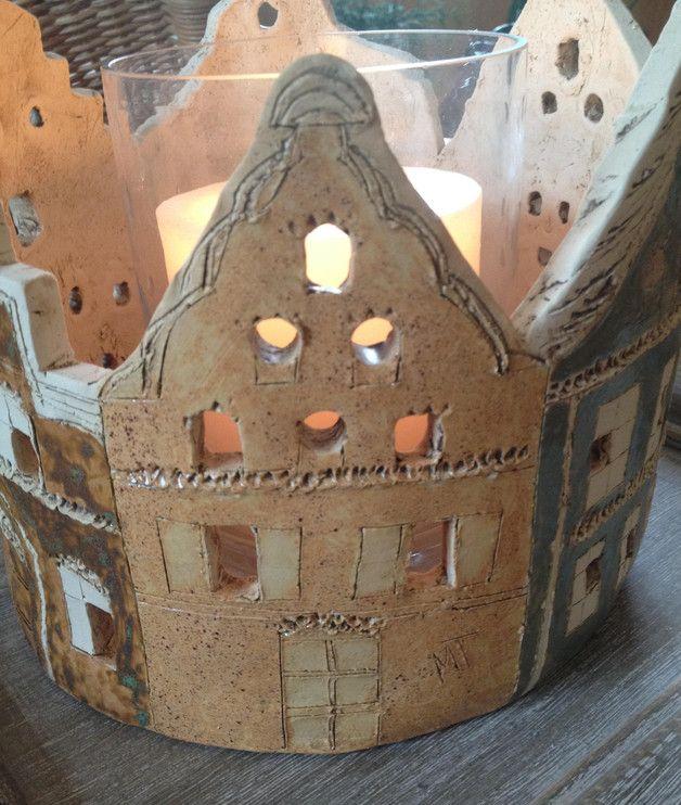 Großes Windlicht mit aufwändig und detailreich gefertigtem hanseatischen Häusermotiv. Die Fenster sind rund und eckig gearbeitet und sind teilweise offen gehalten, sodass die Innenbeleuchtung...