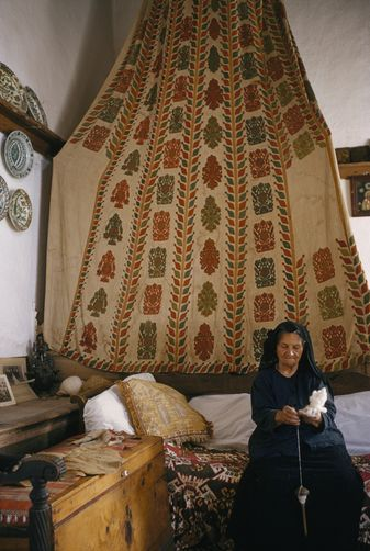 A woman spins yarn in a room filled with family heirlooms.  Location:Lindos, Rhodes, Greece.