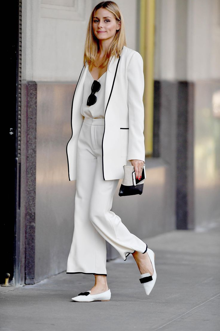 Olivia Palermo in a classic ivory suit trimmed in black with Jimmy Choo pointy-toe flats and a Céline zip pouch.