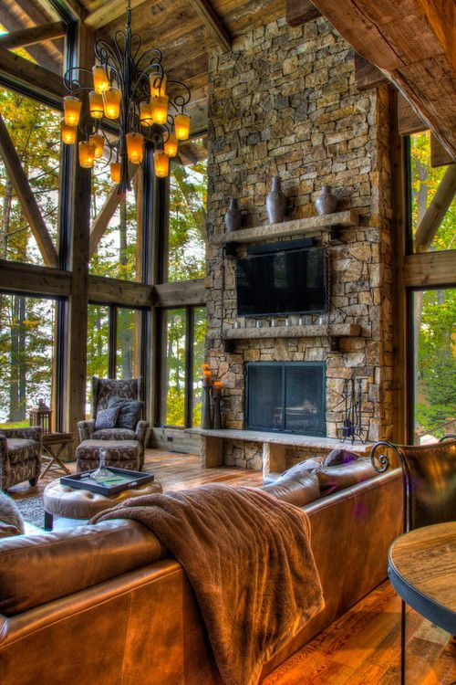 This Rustic cabin makes you feel as if you are outdoors with the rock/stone, wood and awesome windows with trees.