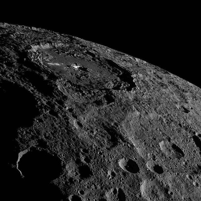 The brightest area on dwarf planet Ceres stands out amid shadowy, cratered terrain in a dramatic new view from our Dawn spacecraft, taken as it looked off to the side of the dwarf planet. Dawn snapped this image on Oct. 16, from its fifth science orbit, in which the angle of the sun was different from that in previous orbits. Dawn was about 920 miles (1,480 kilometers) above Ceres when this image was taken -- an altitude the spacecraft had reached in early October.  Credits…