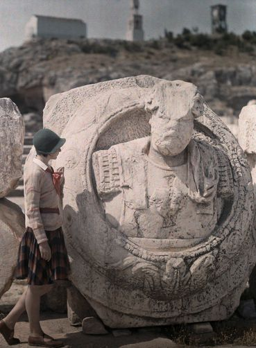 649487. Woman looks at medallion of Roman Emperor at Eleusis.