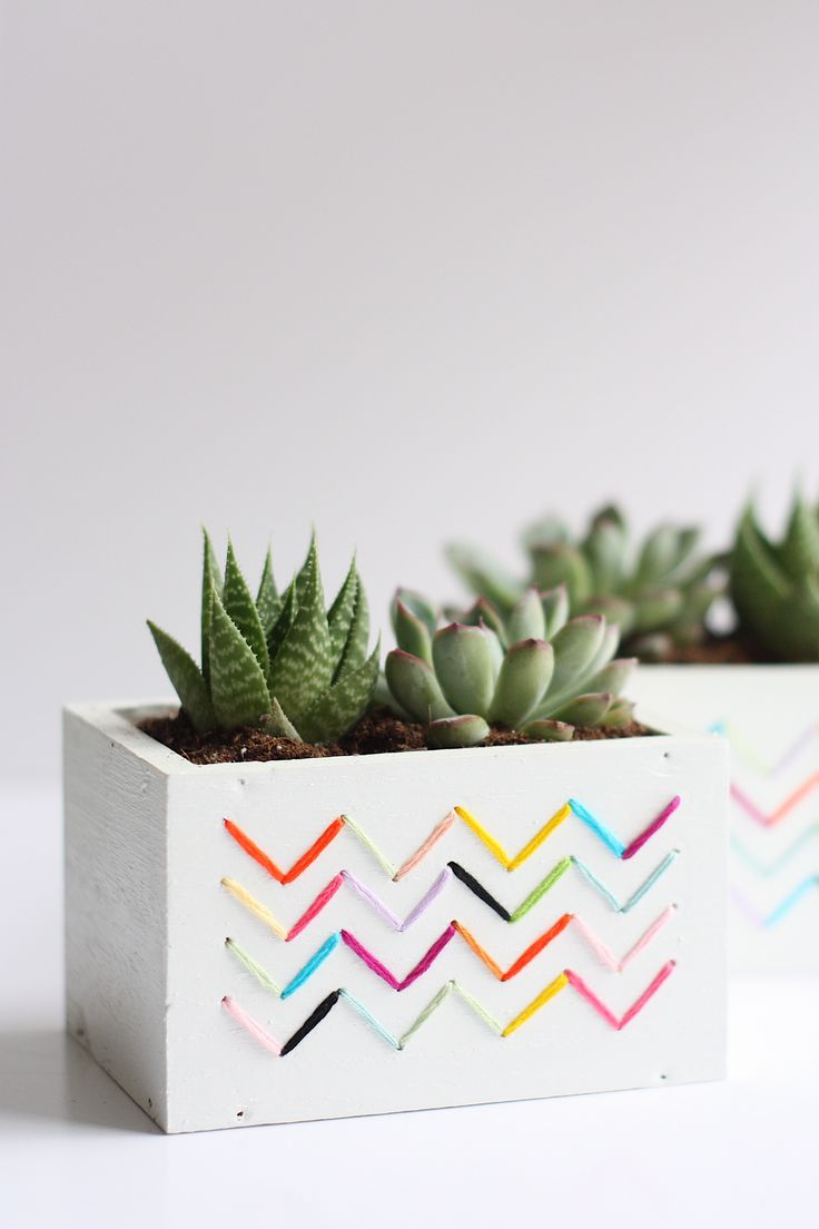 Use a drill and some embroidery floss to make these super cute DIY Stitched Planters that are full of color and texture and are perfect for spring!