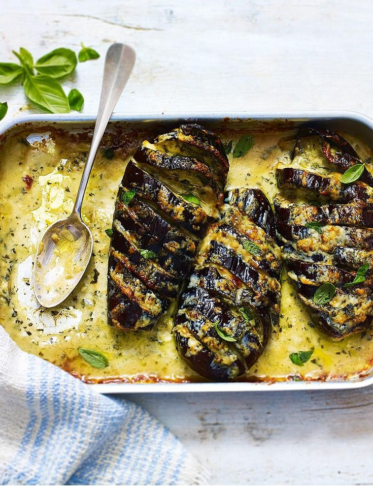 These cheese stuffed roasted aubergines are a super easy vegetarian recipe from Mary Berry's Complete Cookbook. Soaked in a blend of basil and parsley oil, they're filled with chunks of gorgonzola and cheddar then, baked in the oven until crispy at the edges for a simple, quick mid-week meal. Take it one step further and crumble over some Danish blue cheese and extra slices of mozzarella before baking, for an indulgent vegetarian dinner party main course. #Mainmealsforvegetarians