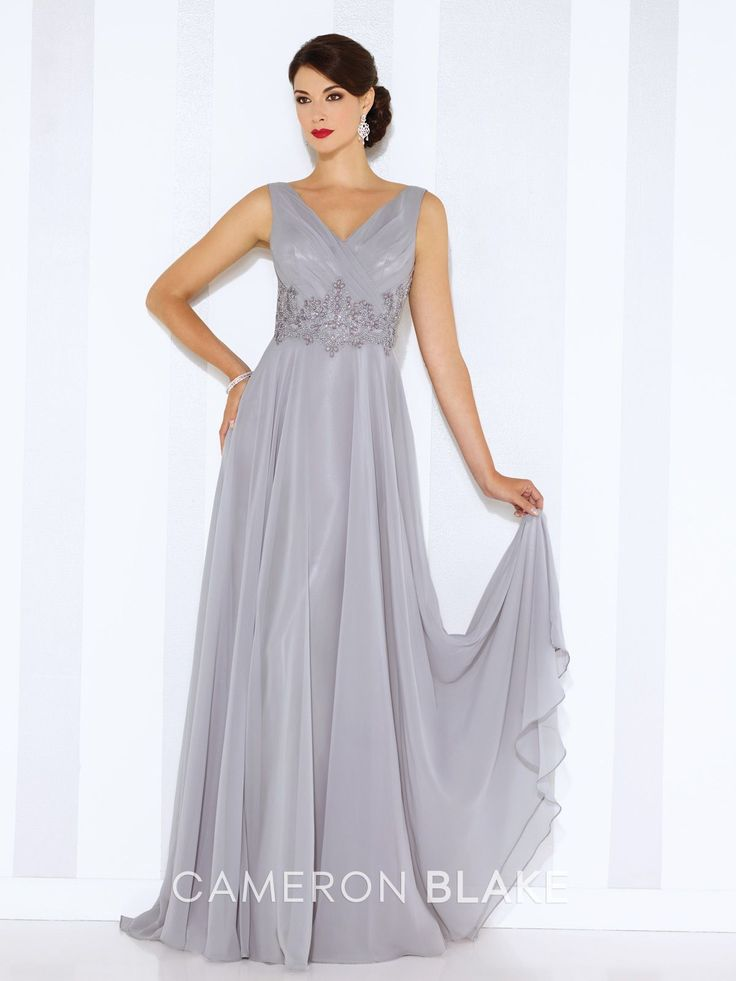 Sleeveless chiffon A-line gown with front and back V-necklines, pleated bodice, hand-beaded motif wraps around natural waist, flyaway skirt with sweep train. Matching shawl included. Sizes:  4 – 20, 16W – 26W Colors: Gray, Water, Royal Blue