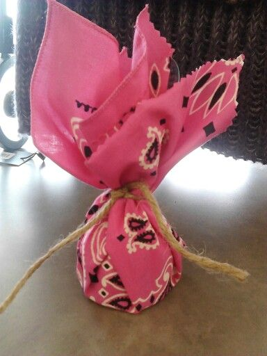 "Cover a balloon weight with a bandanna, for a cowgirl themed party for a little girl. Cut the bandanna into 4  squares to make 4 weights. Squares will be about 10"" x 10""."
