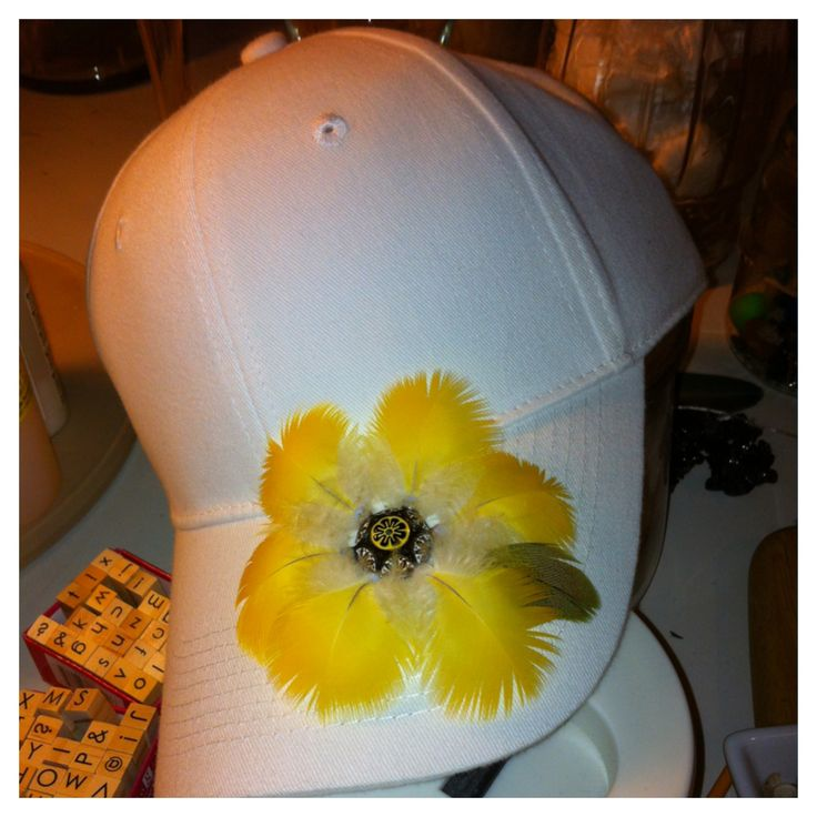 Coco, yellow, blue & gold macaw feathers. Marley, green, nanday conure feathers. Flower baseball cap.