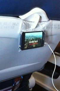 If the back of your plane seat doesn't have TVs, put your phone in a plastic bag and hook it to the back of the tray table (or use a barf bag). | 28 Brilliant Travel Hacks You Need To Know For Summer Vacations