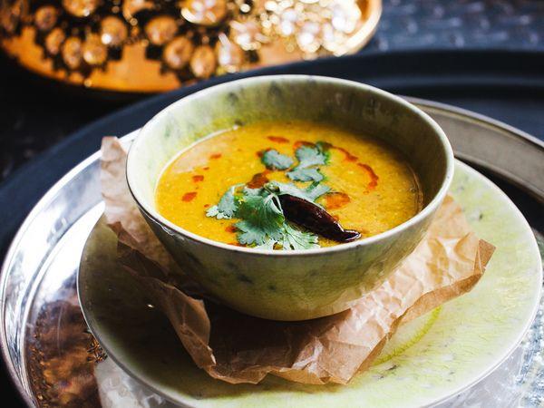 В индийской кухне так много вкусных вегетарианских блюд, что просто глаза разбегаются. На севере Индии зимой бывает холодно, поэтому люди там едят не только лёгкие салаты, но и согревающие блюда. Пример тому – сытный суп дал из чечевицы, который мы предлагаем вам приготовить дома по рецепту индийского ресторана «Жизнь Пи». Ингредиентов там на самом деле очень мало – всего лишь чечевица, чуть-чуть томатов, чеснока и много разных специй.