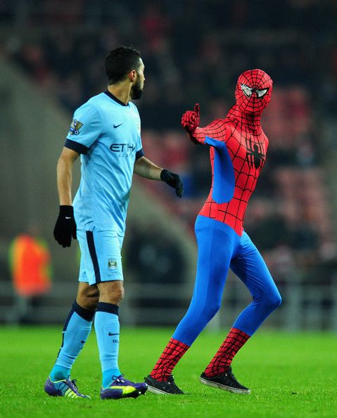A fan dressed in a Spiderman costume invades the pitch and gestures to Manchester City's Martin Demichelis