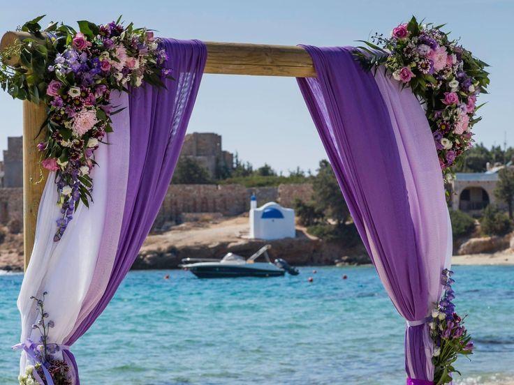 Every style is possible - beautiful arch on Alyko Beach Naxos Greece for a #destinationwedding #greecewedding Purple gauze and flowers