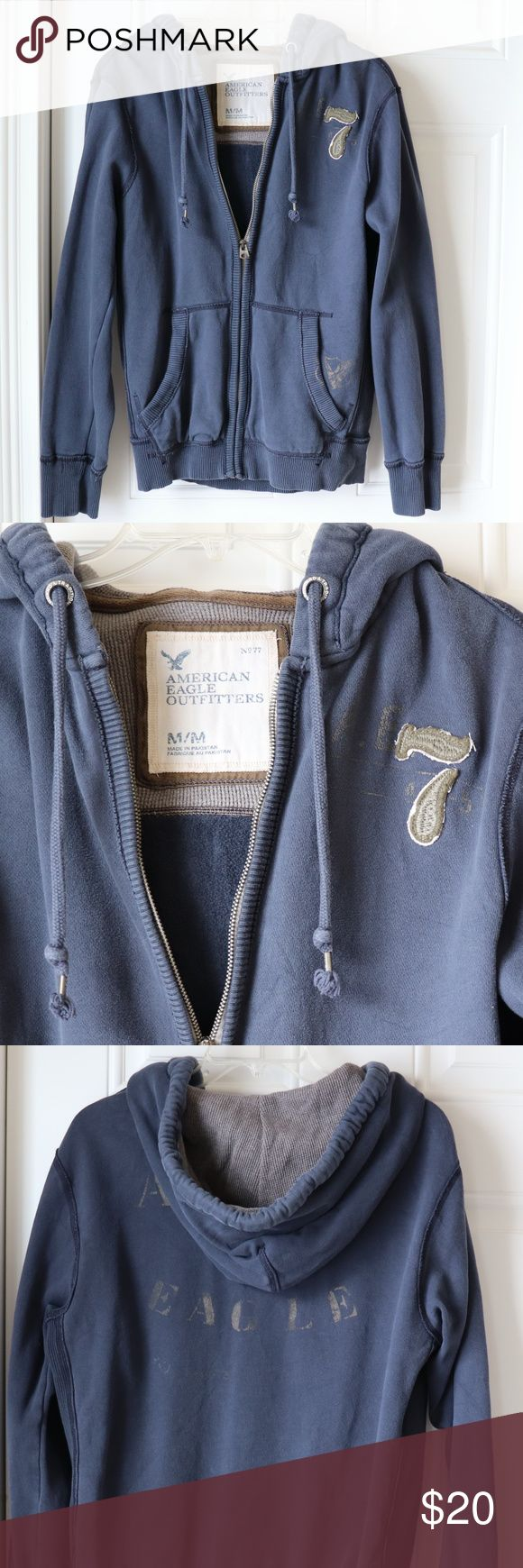 """American Eagle Men's Sweatshirt Hoodie Medium American Eagle Men's Medium hoodie. Zipper front with 2 pockets.  Navy with gray embossed design on left hip and across the back.  Olive embroidered """"7"""" on left chest.  Condition: Gently used.  Material: 84% Cotton - 16% Polyester.  All measurements are approximate: Underarm to Underarm across the front: 22""""  Top of shoulder to bottom edge: 27"""" Sleeve length: 25""""  Pet free and smoke free home. American Eagle Outfitters Shirts Sweatshirts…"""