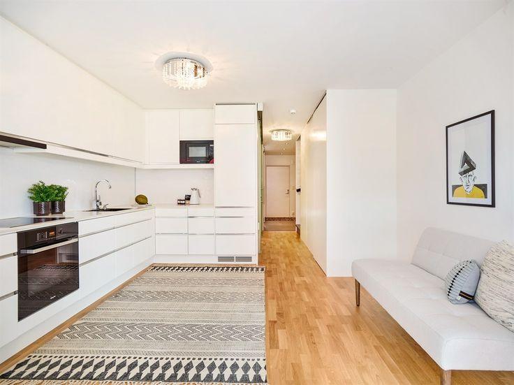 Kjøkkeninnredning fra Drømmekjøkkenet med glatte fronter, kompaktlaminat benkeplate, underlimt kompositt oppvaskkum, komfyrvakt, Røroshetta ventilator, integrerte hvitevarer, og kitchenboard på vegg over benk og belysning under takhøye overskap. Det er godt med skap- og benkeplass på kjøkkenet.