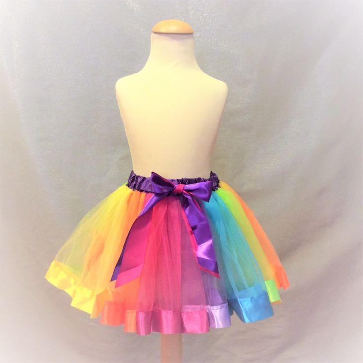 Prachtig gekleurde regenboogtutu met elastische taille en losse stroken tule voor een mooi wijd effect. Met dubbelgekleurde (roze en lila) sierstrik op het voorpand, afgewerkt met satijnen stroken langs het onderpand.   Model: Rainbow