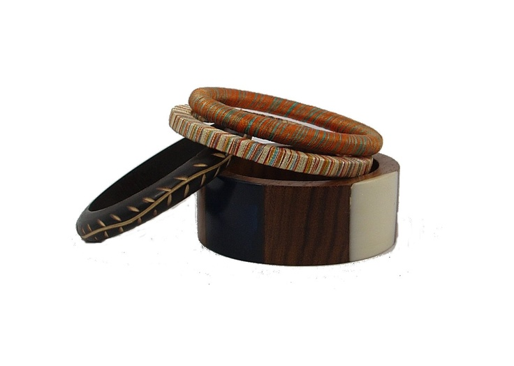 A perfect set for a fashionista on budget. This set of four has unusual bangles. There is one bangle with hand carved vine design, a pair of pure silk bangles hand wrapped, in multi color threads. There is one bold geometric pattern wide wood bangle. Wear them all together for a classy well travelled look.