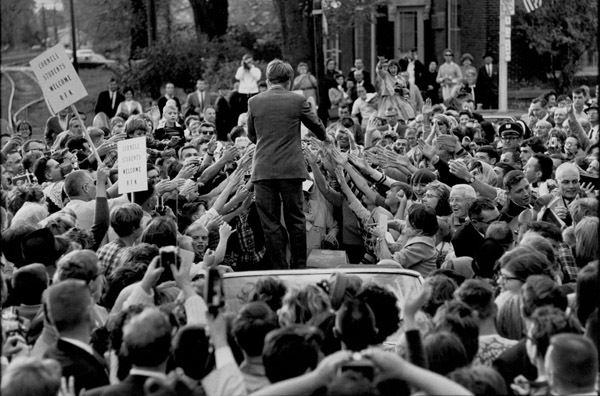 Senator Robert F. Kennedy standing above a sea of outstretched hands on a swing through the Midwest. Marion, Iowa, 1966.