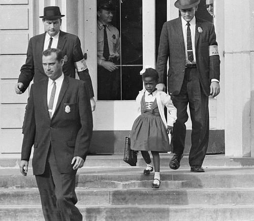 Little Ruby Bridges, the first African-American child to attend an all-white elementary school in the American South, escorted by US Marshals for her safety. New Orleans, 14 November 1960.