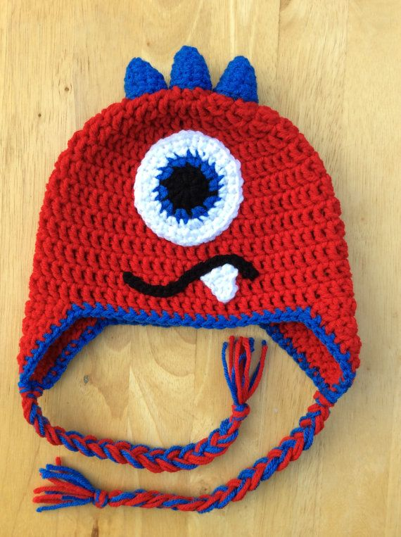 Kids of all ages will look adorable in a crochet monster hat! This one-eyed, three-horned crochet monster hat in Cherry Red and Blue can be made to fit anyone - from babies and toddlers all the way up to grown ups who are young at heart! The hat has earflaps and braids with tassels but can be made as a beanie hat if desired.  All monster pieces (eye, horns, mouth, tooth, and braids) have been hand-sewn/knotted onto the hat. Horns have been stuffed with polyester sutffing. No glue has been…