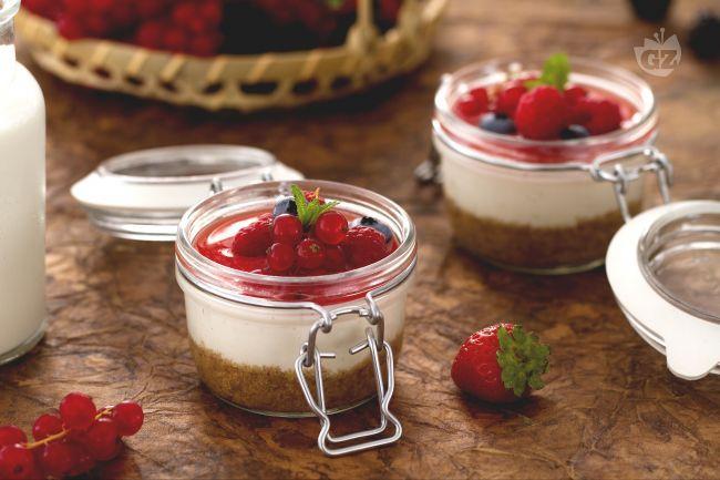 Le cheesecake nel barattolo sono delle piccole delizie al cucchiaio realizzate con una base di biscotti secchi e crema di yogurt con frutti di bosco.
