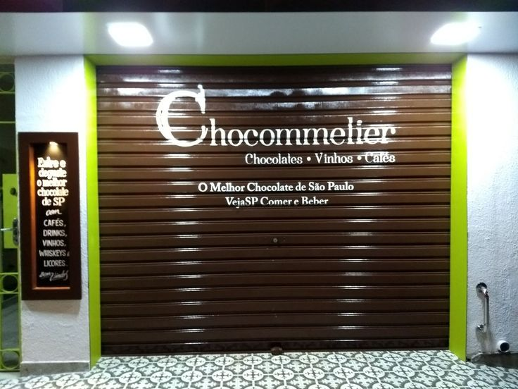 Pintura de escritas do logo Chocommelier com frase feito em portão de enrolar de loja de chocolate.
