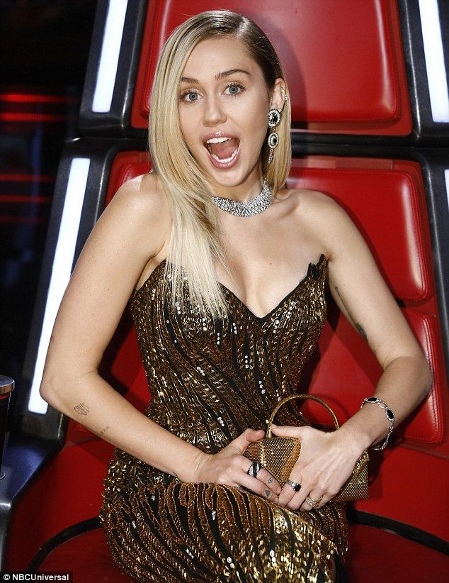 Glamorous: Miley, 24, flaunted her gravity-defying cleavage in her plunging garment, embel...