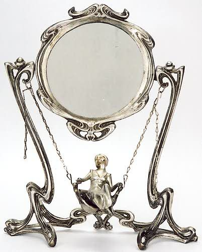 A SILVERED-BRONZE FIGURAL VANITY MIRROR, in the Art Nouveau taste. The circular mirror on frame from which are chains supporting swing chair with woman in long gown