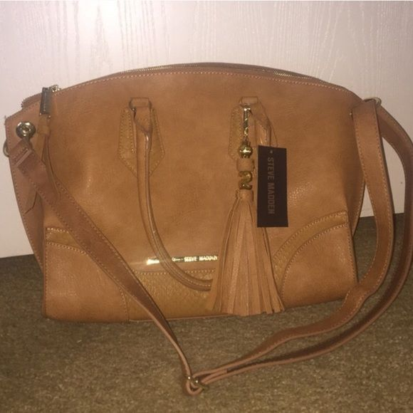 """NWT!! Steve Madden Handbag New with tags! Steve Madden handbag. Camel color. Gold hardware. Gorgeous detachable tassel. Adjustable should strap along with handles. 14"""" across base, 18"""" across at the top. 12"""" from top to bottom. 1 zippered pocket inside. 2 smaller open pockets inside. Tags attached. $98.00 Steve Madden Bags Satchels"""