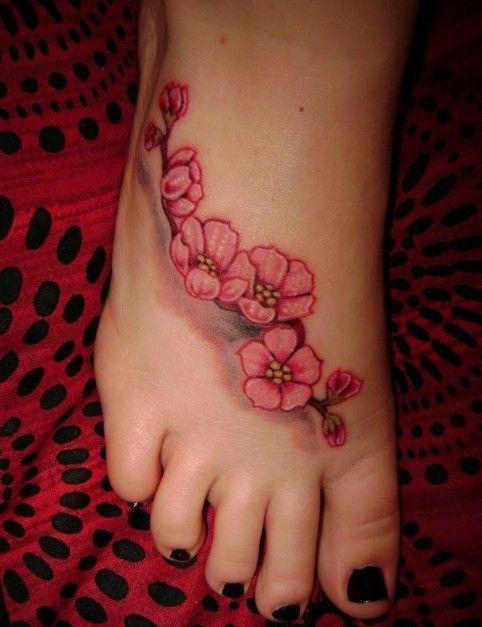 Petite fleur de cerisier tatouée sur le dessus du pied