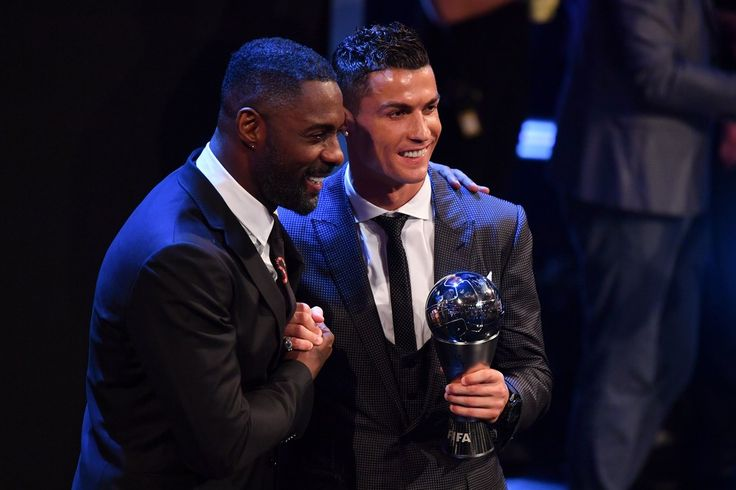 British actor Idris Elba (L), acting as host, shakes hands with Real Madrid and Portugal forward Cristiano Ronaldo after Ronald wins The Best FIFA Men's Player of 2017 Award during The Best FIFA Football Awards ceremony, on October 23, 2017 in London. / AFP PHOTO / Ben STANSALL