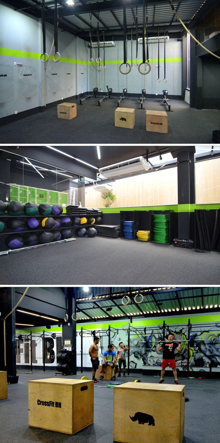 Academia CrossFit BH 3 - Área de treino em piso emborrachado, paredes pintadas de preto, verde e cinza claro. Instalações, telhado e estrutura aparentes. Galpão em estrutura metálica e telha sanduíche. Painel de madeira no corredor.