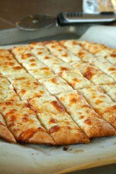 Pizza deeg met knoflookboter en kaas. Koop pizzabodem mix of neem die van bijvoorbeeld dannerol uit de koeiling. Rol hem uit tot pizza formaat, Smeer er knoflook/kruidenboter over heen en parmasaanze kaas met mozzerala en een snufje zout en peper.. afbakken in de oven en klaar!
