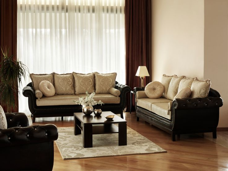 An elegant living room with button-tufted sofas and ornate, luxurious cushions. The dark leather and wood contrast beautifully with the light, warm hardwood flooring. The circular and rolled pillows, along with the button-tufting and rolled arms, give this space a delightfully transcendent appearance.