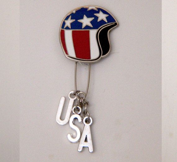 EASY RIDER SINGLE MONO EARRING.    RECEIVE 10% OFF WITH CODE: WELCOMESALE2017     THE STORY:  Dennis Hoppers 1969 revolutionary film Easy Rider continues to be a source of major inspiration at MITCHUMVSBOGART. Dennis Hopper is the icon above all others!  This single earring is modelled on the original Captain American Helmet worn by Peter Fonda in Easy Rider. The silver charms spell USA.  MATERIALS:  Enamel Pin base - Measures approximately 1 Safety Pin Silver letter charms