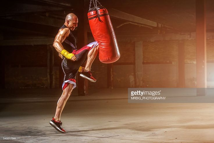 MMA fighter practicing knee kick to punching bag