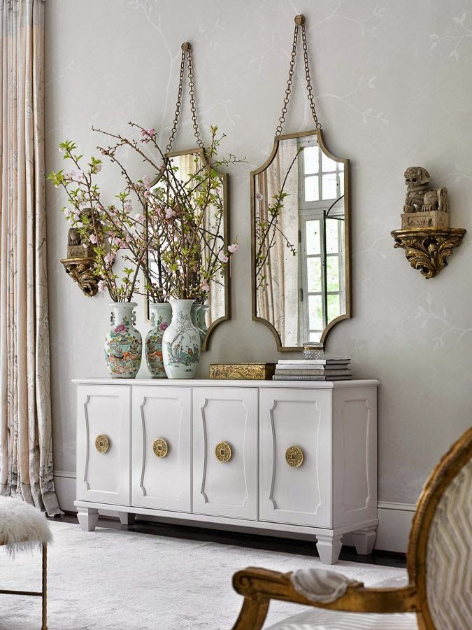 Double mirrors with asymmetrical styling on the buffet. Pretty neutral tones.