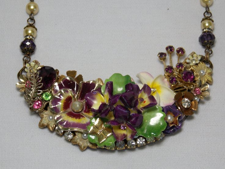 I started this necklace with a vintage English bone china brooch with a cluster of violets with yellow centers.. I have added other flowers including a purple/yellow pansy and small flowers with pearls and/or rhinestones. Pieces of vintage rhinestone chain are along the bottom edge and along the entire top edge (hard to see in pics). I created the rosary style chain using purple crystal beads and light yellow glass pearls. The necklace is not overly large, 3 1/2 inches wide and...