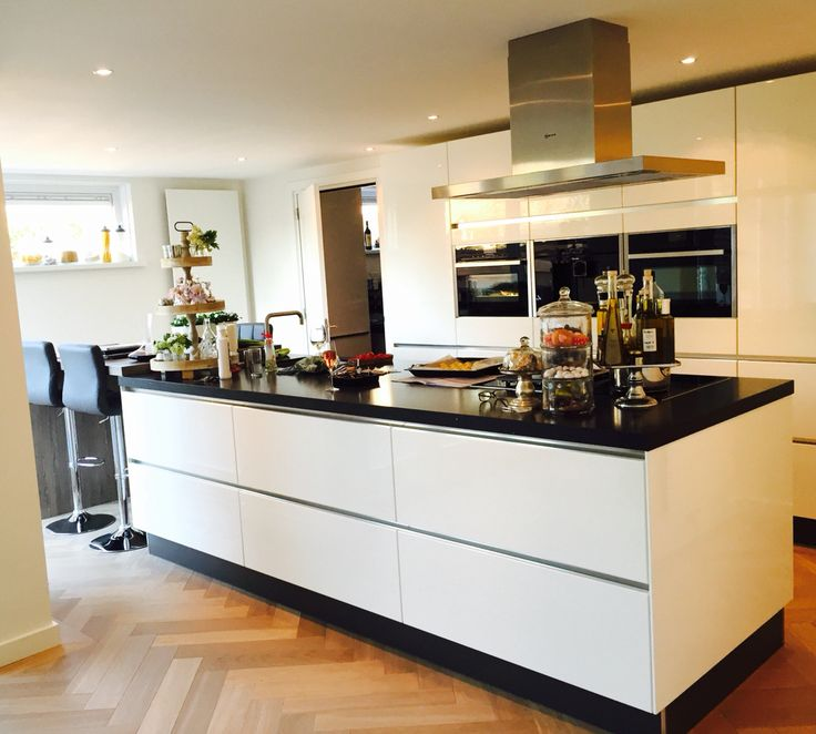 Systemat AV4030 greeploos hoogglans gelakt witte keuken, met NEFF combistoomoven, compacte oven met magnetron, koffiezetter. Opgedikt werkblad van 5cm met eraan een houten bar.