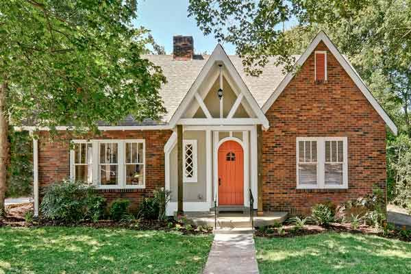 thisoldhouse.com | from Curb Appeal Boosts for Every Budget - I love the orange front door and the exposed/open roof woodwork
