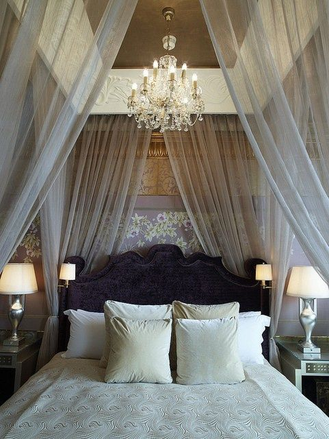 Silvery sheer fabric bed hangings make for a dreamy boudoir. (Check out the gold and silver wallpaper in the background.)