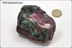 La ZOÏSITE appartient au groupe des silicates. Elle contient du calcium, de l'aluminium et du silicium. Elle présente une forme massive ou des cristaux prismatiques striées. On trouve de la ZOÏSITE verte, violette ou beige.   Le  RUBIS appartient au groupe des oxydes. Il contient de l'aluminium et une quantité minimale de chrome. Le rubis se présente généralement sous la forme de cristaux allongés avec des faces prismatiques. Sa couleur rouge provient de la présence d'oxyde de chrome.