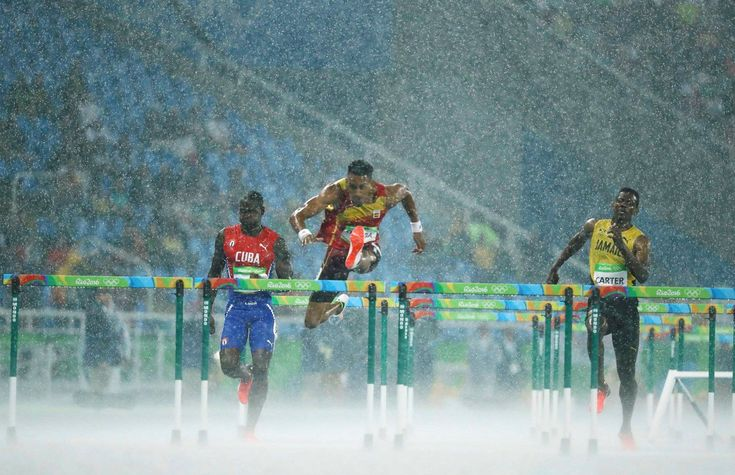 Jhoanis Portilla of Cuba, Orlando Ortega of Spain and Deuce Carter of Jamaica compete in the rain during the 2016 Rio Olympics Men's 110m Hurdles in Rio de Janeiro, Brazil, Aug. 15, 2016.
