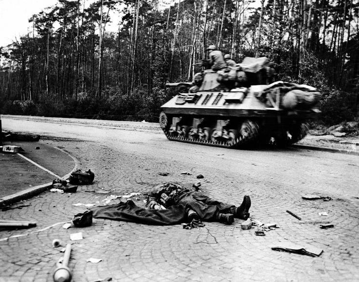 afp.1945.03.27. - Frankfurt am Main, Németország: az amerikai hadsereg hatodik páncéloshadosztályának egyik tankaj egy halott német katona mellett - II. világháború,