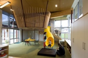 """Te Kura Kaupapa Maori & Te Kohanga Reo O Mana Tamariki, Palmerston North by Tennent and Brown Architects. A """"nest"""" hovers over the space, while a yellow slide winds down from the mezzanine to the ground floor."""
