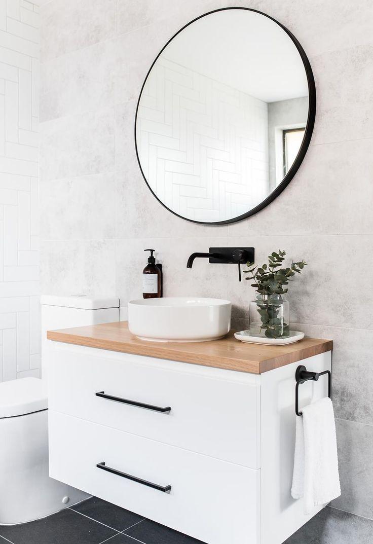 Weißes Badezimmer mit Rundspiegel und Waschtisch aus Sperrholz. Rundes Becken mit Akzent