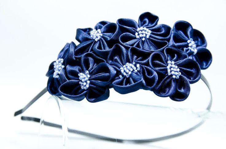 Čelenka Rozalia temně modrá Kovová čelenka o šířce 0,5cm,barva černá. ( je možné objednat i stříbrnou čelenku- uveďte do poznámek) 6 ručně šitých saténových květinek vtemně modrébarvě. Středy květů jsou vyšity rokajlem a perličkami. Velikost květů jsou3 - 4 cm.Celková délka aplikace cc 11-15cm. Pro pohodlnější nošení jsou květy podlepeny filcem. ...