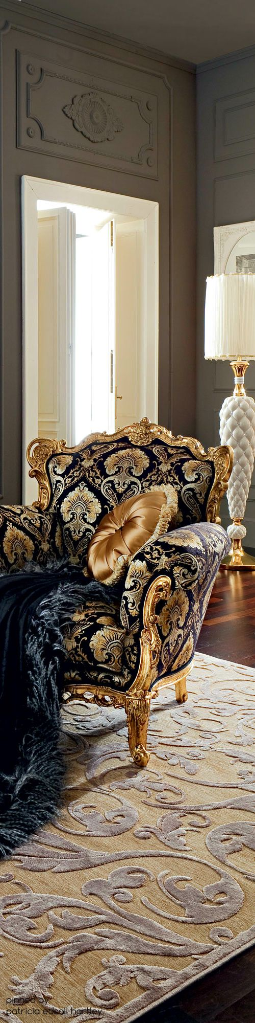Beautiful chair with the gold trim, gold round pillow and the navy throw placed over the chair